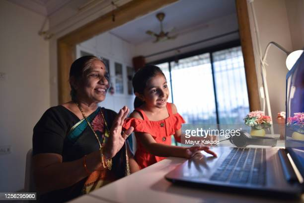 grandmother and granddaughter video conferencing using laptop - indian ethnicity stock pictures, royalty-free photos & images