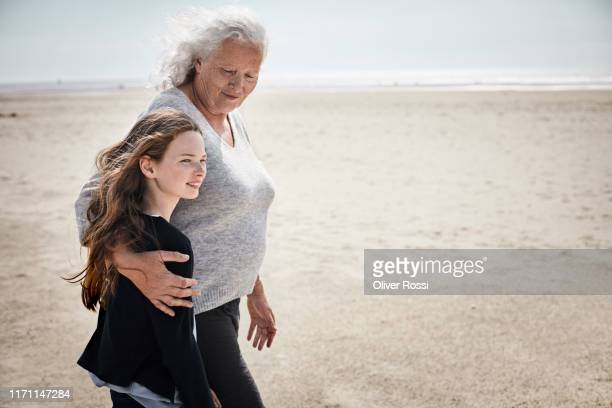 grandmother and granddaughter walking on the beach together - schleswig holstein stock pictures, royalty-free photos & images