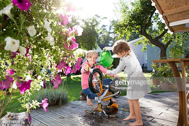 Grandmother and granddaughter washing bicycle on garden terrace