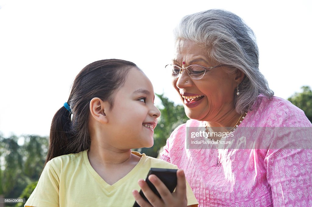 Grandmother and granddaughter with a mobile phone : Stock Photo