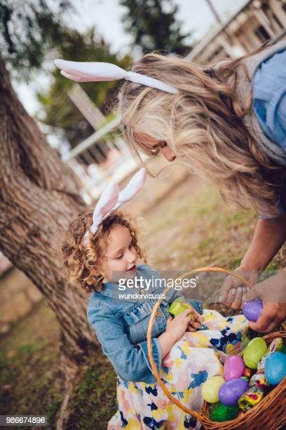 grand-mère et sa petite-fille avec panier d'oeufs de pâques dans le jardin - chasse aux oeufs de paques photos et images de collection