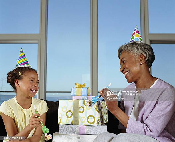 Grandmother and granddaughter (8-10) with gifts and party blowers