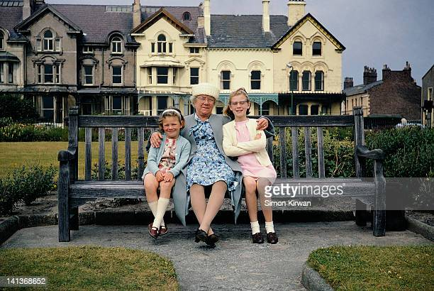 grandmother and grand-daughters on park bench - liverpool england - fotografias e filmes do acervo