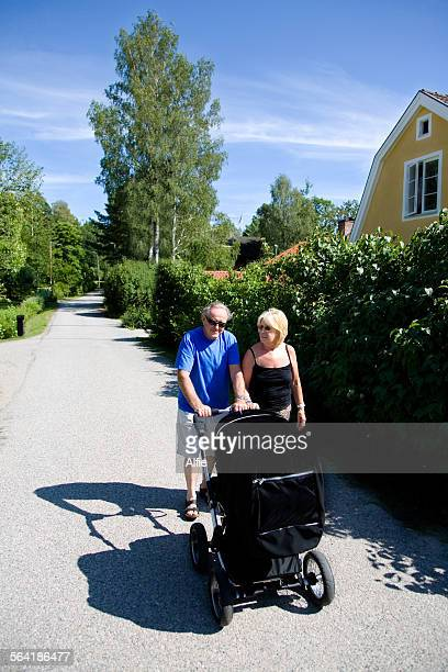 Grandmother and grandfather out walking baby boy in a pram
