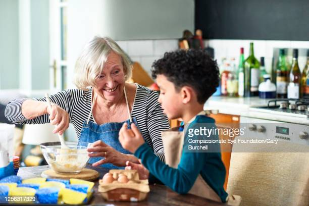 grandmother and grandson baking cupcakes - senior women stock pictures, royalty-free photos & images