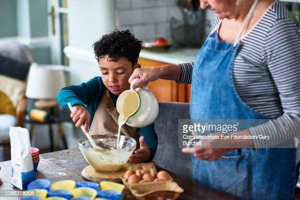 grandmother and grandson baking cupcakes - active lifestyle stock pictures, royalty-free photos & images