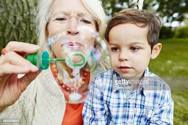 Grandmother and grandson blowing soap bubbles
