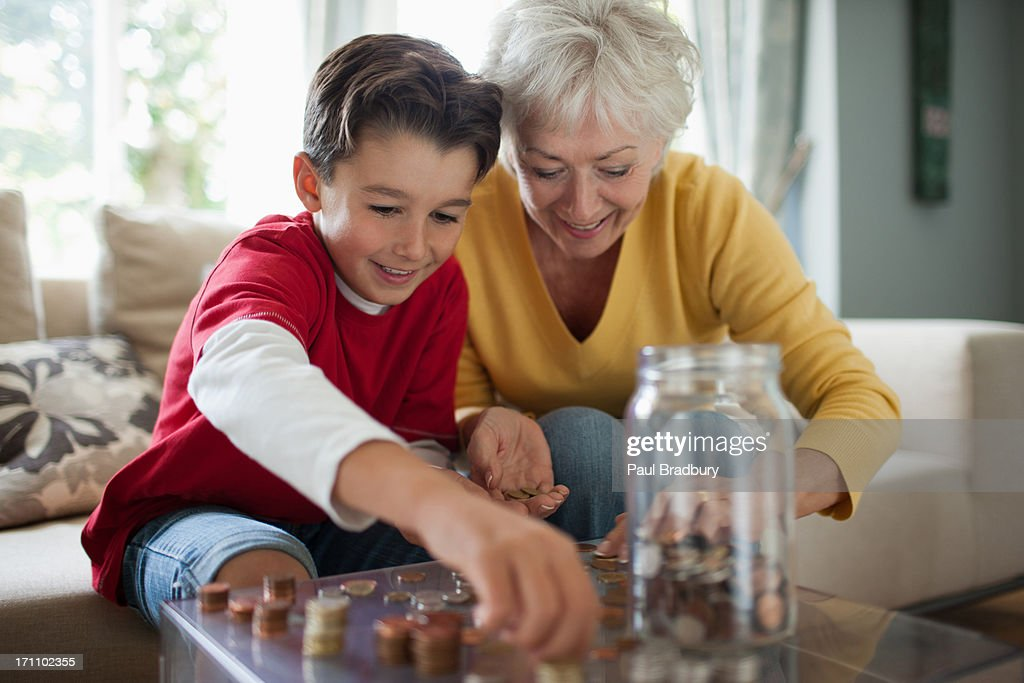 Grandmother and grandson counting coins : Stock Photo