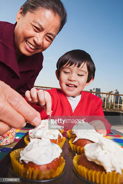 Grandmother and grandson decorating cupcakes