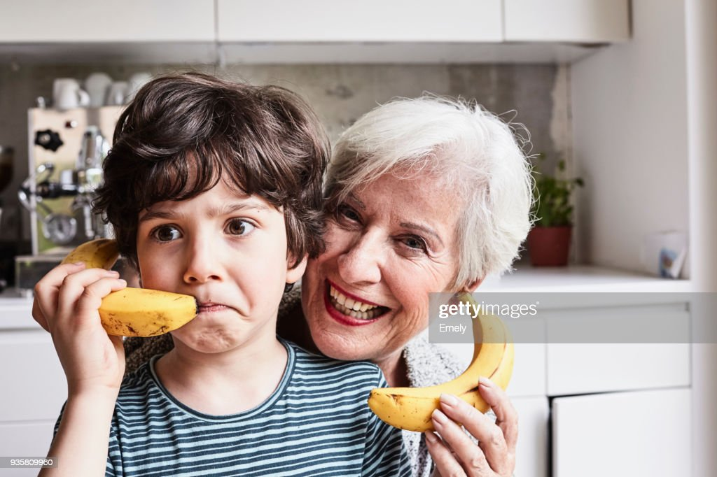 Grandmother and grandson fooling around, using bananas as telephones, laughing : Stock Photo