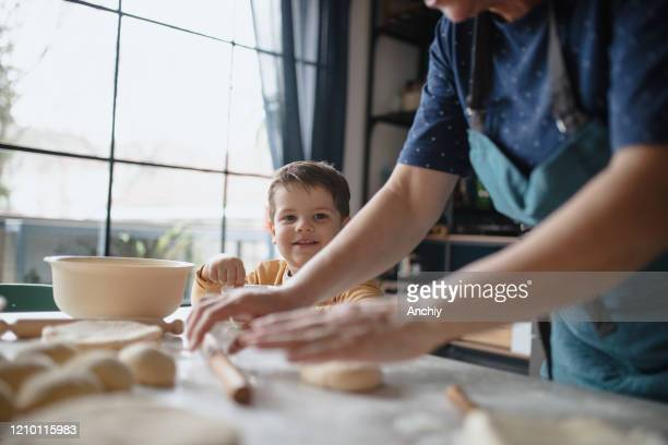 grandmother and grandson having fun preparing dough in the kitchen - baking bread stock pictures, royalty-free photos & images