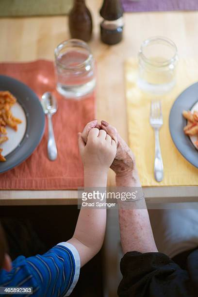 Grandmother and grandson holding hands at dinner table