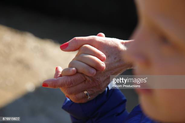 grandmother and grandson holding hands - british granny stock photos and pictures