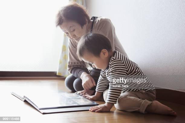 祖母と孫の写真のアルバムを一緒に見て