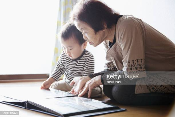 grandmother and grandson looking a photo album together - childhood photo album stock photos and pictures