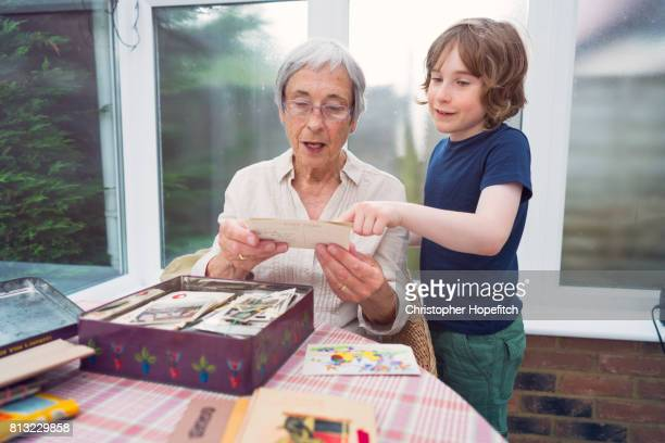 grandmother and grandson looking through old photographs - memorial stock pictures, royalty-free photos & images