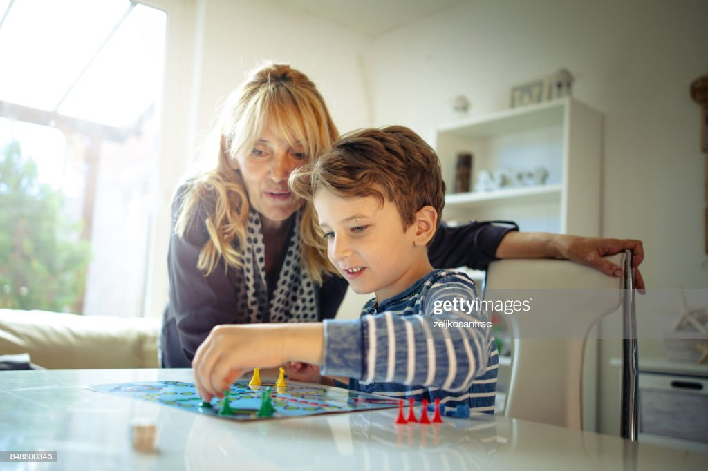 Grandmother and grandson playing boards game : Stock Photo