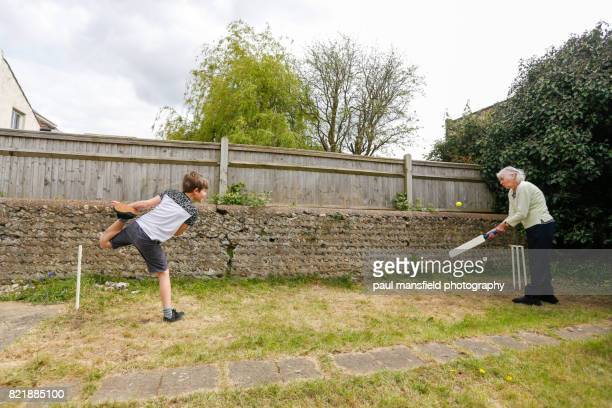grandmother and grandson playing cricket in a garden - wicket stock pictures, royalty-free photos & images