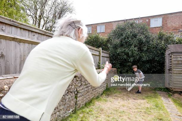 Grandmother and grandson playing cricket in a garden