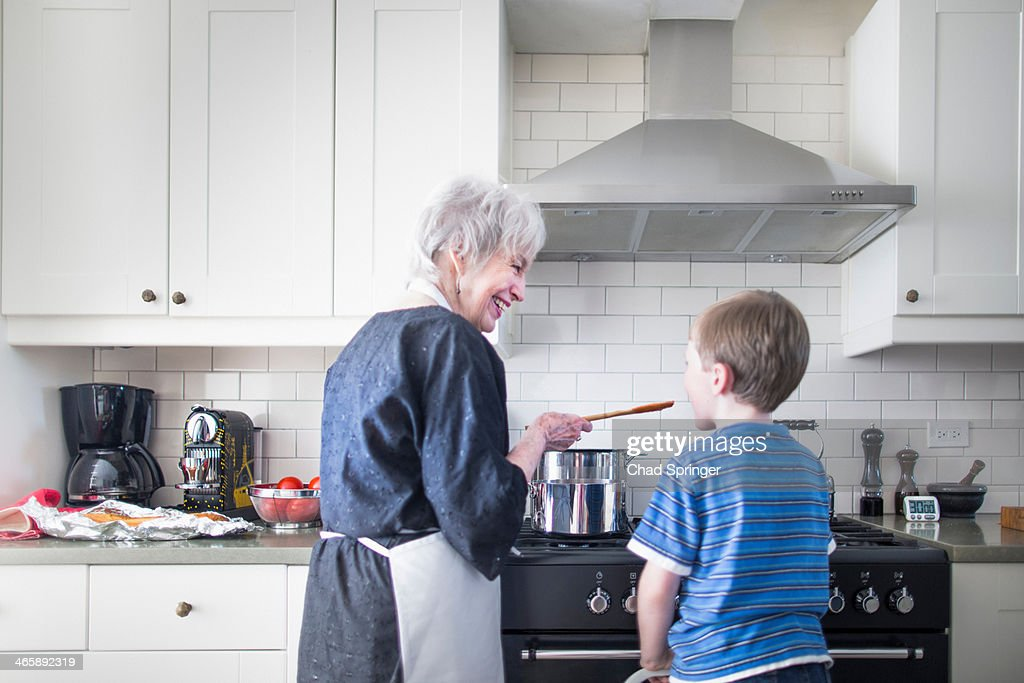 Grandmother and grandson preparing food at home : Stock Photo