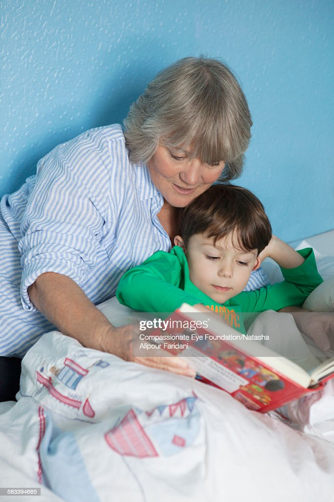 Grandmother and grandson reading book in bed : Stock Photo