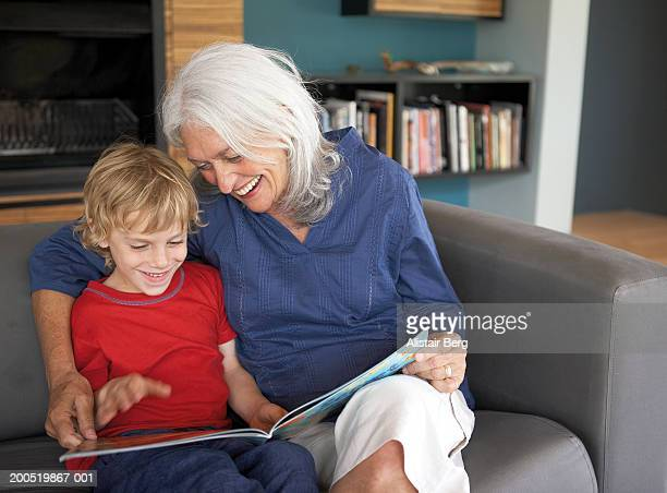 Grandmother and grandson (5-7) reading book on sofa, smiling