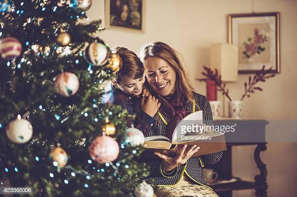 grandmother and grandson reading fairy tales on christmas - cuento de hadas fotografías e imágenes de stock