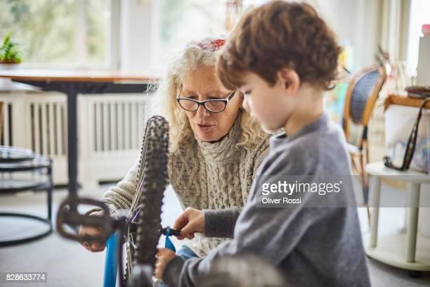 Grandmother and grandson repairing bicycle at home