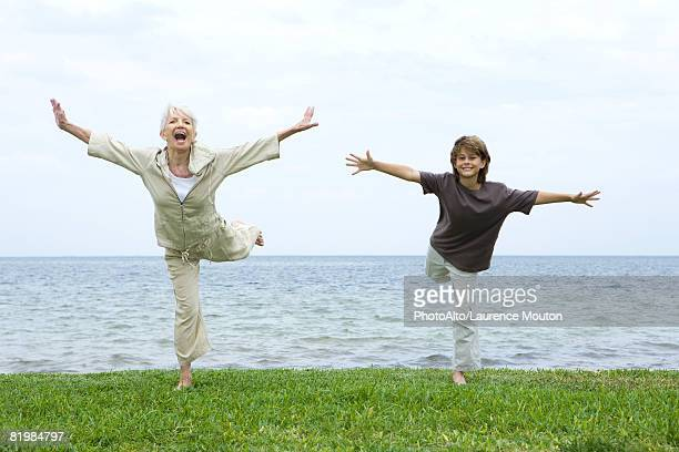 grandmother and grandson standing on one leg, arms outstretched, both smiling at camera - standing on one leg stock pictures, royalty-free photos & images