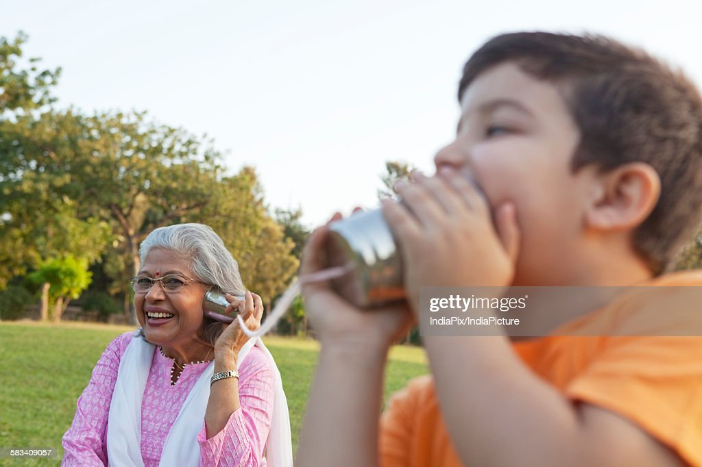 Grandmother and grandson talking through tin cans : Stock Photo