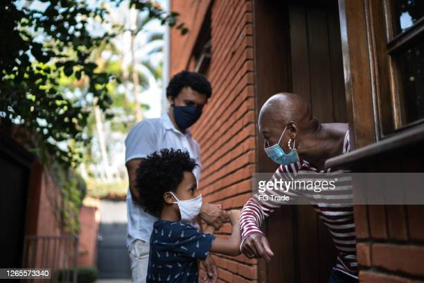 grandmother and grandson using elbow greeting - social gathering stock pictures, royalty-free photos & images