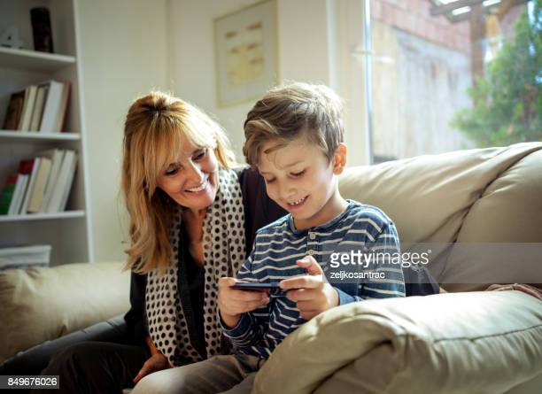 Grandmother  and grandson using mobile.