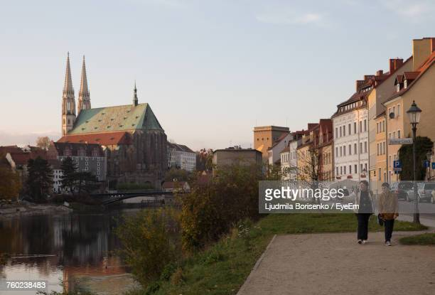 Grandmother And Grandson Walking On Footpath By River At Gorlitz Town