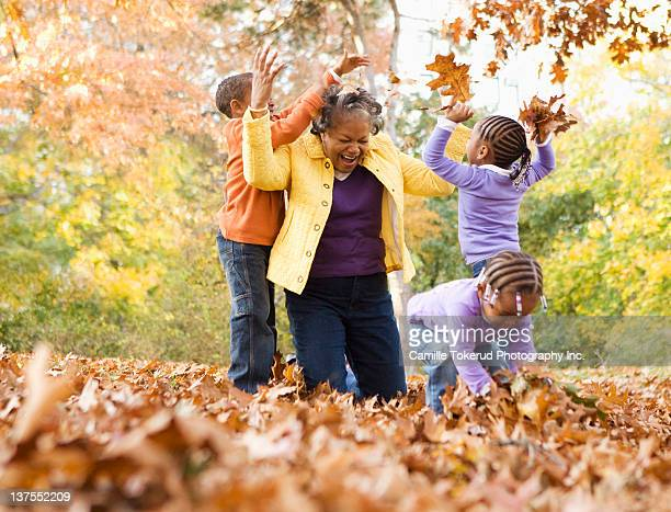 Grandmother and grandsons playing with leaves