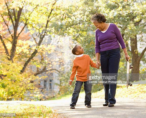 Grandmother and granson walking in park smiling