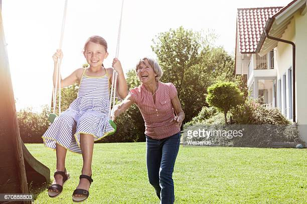 Grandmother and happy granddaughter on swing in garden