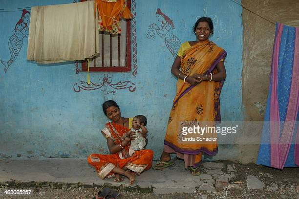Grandmother and her daughter and son relax on the sidewalk of their home in Titigarh on the outskirts of Kolkata. The walls are brightly colored in...