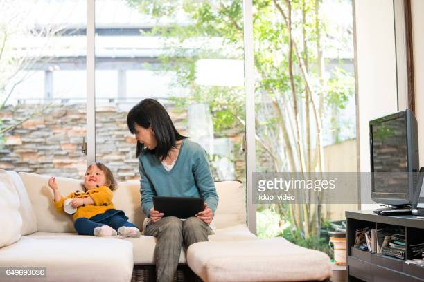 grandmother and her grandchild relaxing at home - tdub_video stock pictures, royalty-free photos & images