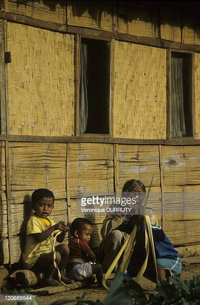 Grandmother and her grandchildren in a village near Rantepao in Toraja land Sulawesi Indonesia The traditional bamboo toraja house is called tongkonan