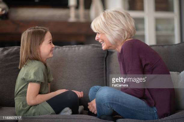a grandmother and her granddaughter clap hands and play together on the couch. - fat granny stock pictures, royalty-free photos & images