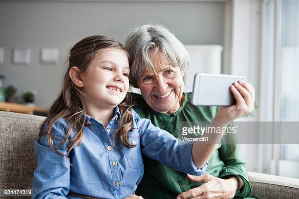 Grandmother and her granddaughter sitting together on the couch taking selfie with smartphone