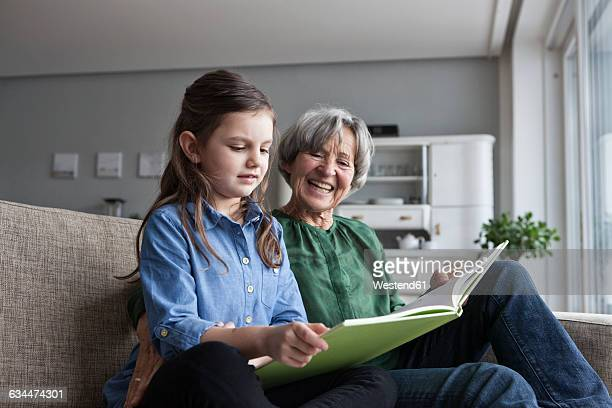 Grandmother and her granddaughter sitting together on the couch with a book