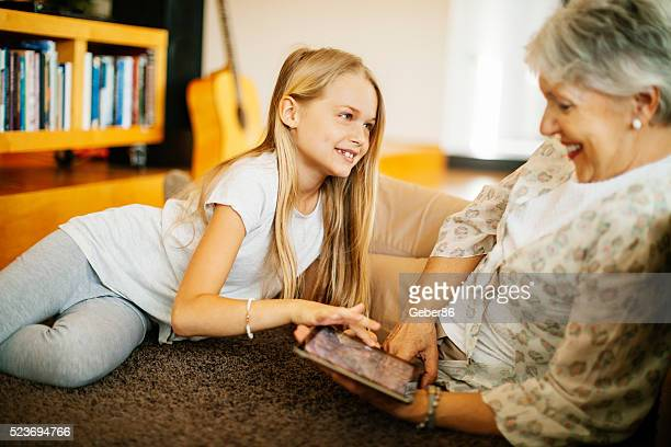 Grandmother and her granddaughter using a tablet at home