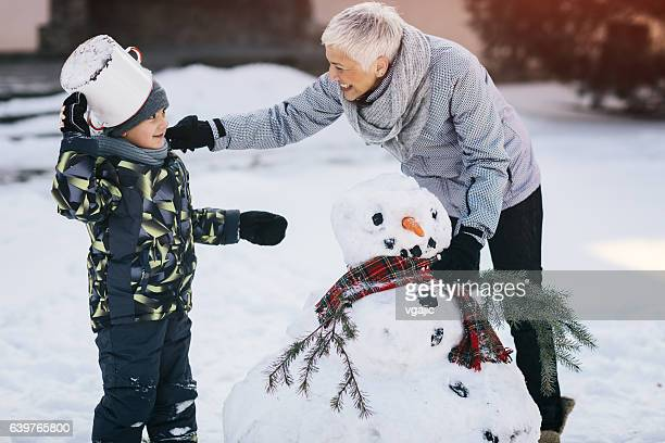 Grandmother And Her Grandson Making Snowman