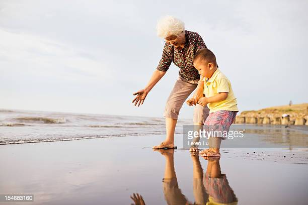 Grandmother and little boy are playing on beach