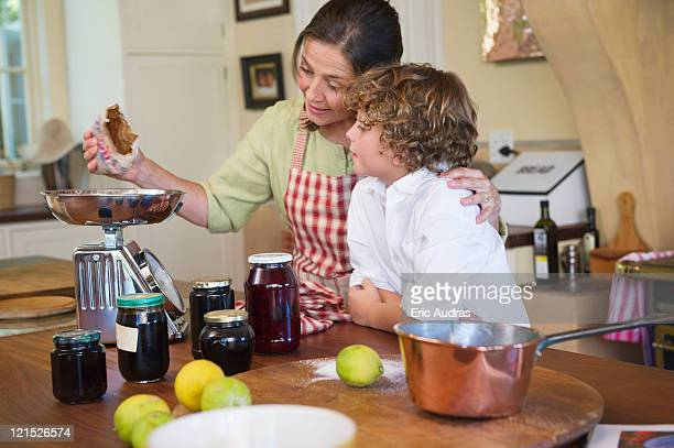 Grandmother and little boy cooking food at kitchen