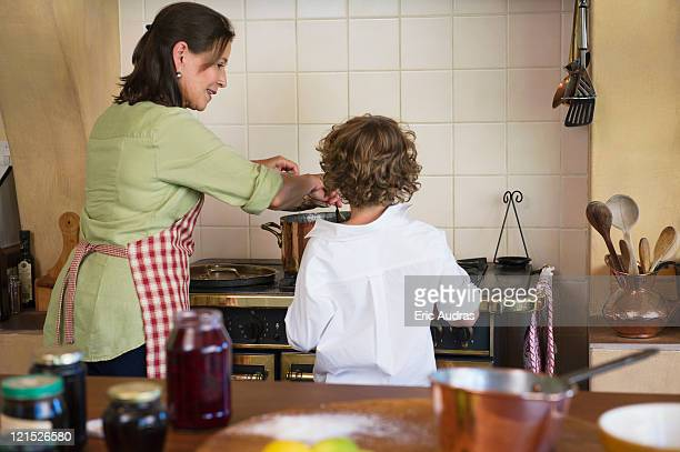 Grandmother and little boy cooking food together at home