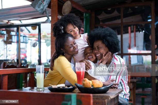 grandmother and mom hug their two children from 7 to 8 years old all with dark skin and afro hair all are sitting in typical colombian food restaurant at the table have empanadas and blackberry juice - 25 29 years stock pictures, royalty-free photos & images