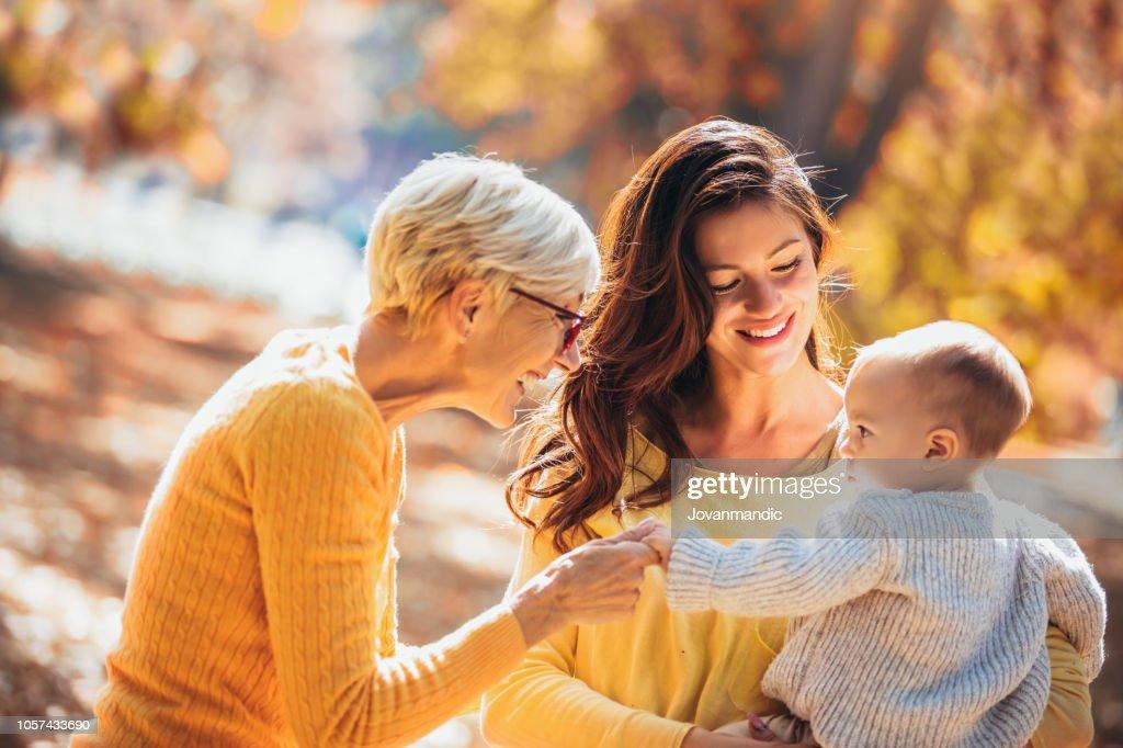 Oma en moeder lacht op baby in herfst park. : Stockfoto