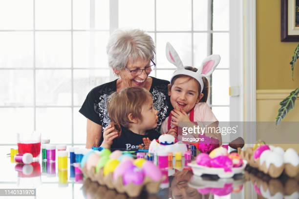 grandmother and sister and brother painting easter eggs - dirty easter stock pictures, royalty-free photos & images